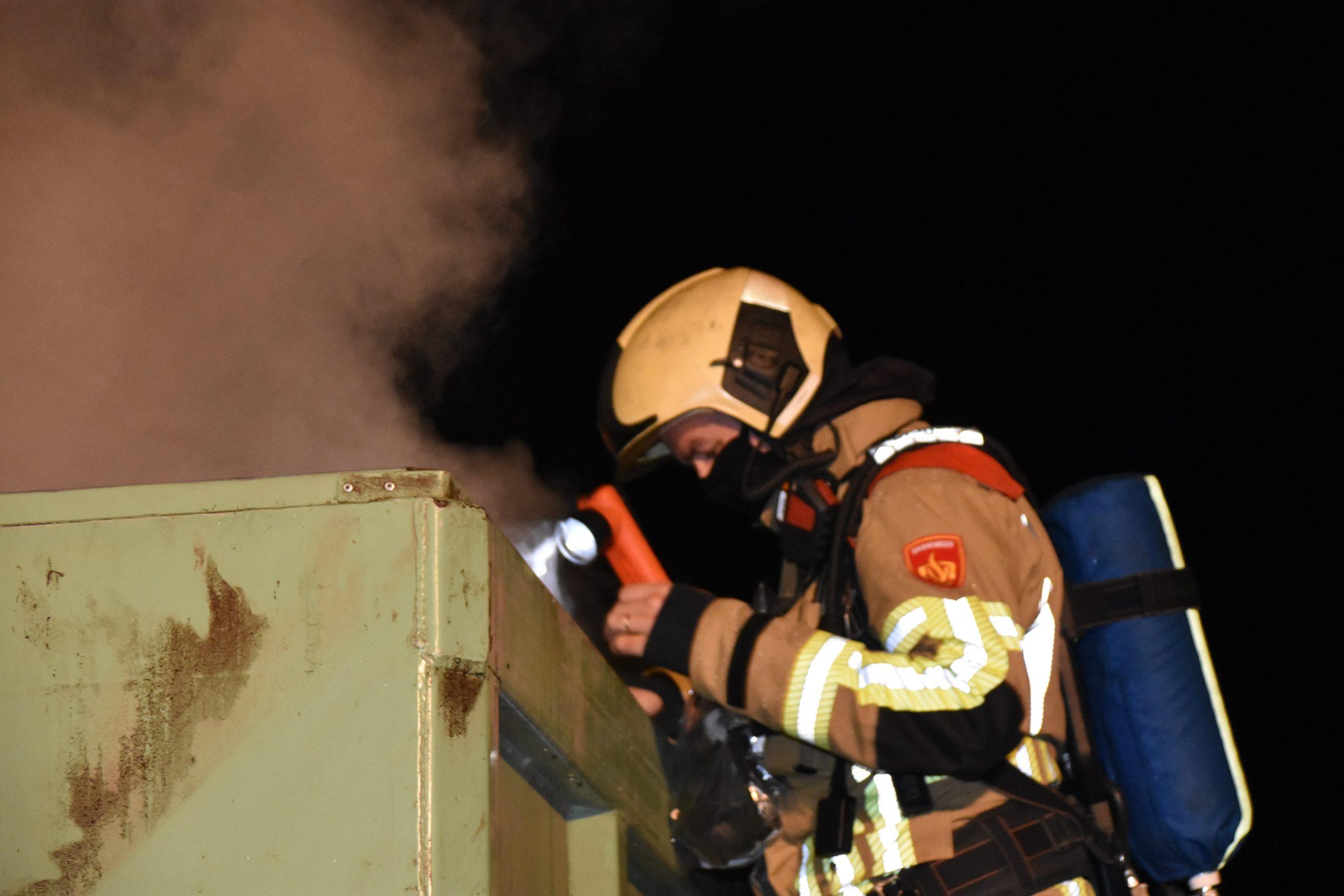 Container met houtvezels in brand